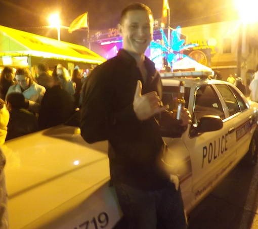 Young man boldly holds up beer nearcop car during New Years on Main Street in Daytona / Headline Surfer®